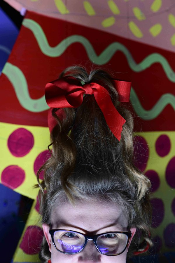 "Ashlynne Hollis, 15, daughter of Wendy Hollis and Roy Hollis, sits on the Zion Church float while waiting for the Columbus Christmas Parade to start Dec. 2 at the Columbus Soccer Complex. Hollis' aunt did her hair like Cindy Lou Who from ""How the Grinch Stole Christmas"" to fit with the church's Dr. Seuss themed float. / Photo by: Jennifer Mosbrucker/Dispatch Staff"