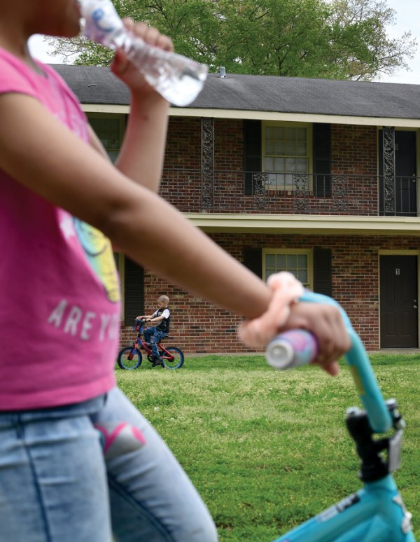 LeLe, 7, takes a drink of water while she and her little brother C.J., 6, play outside Thursday next to their family's apartment in Columbus. All schools in Mississippi will remain closed until April 17 to prevent the spread of COVID-19. / Photo by: Jennifer Mosbrucker/Special to The Dispatch