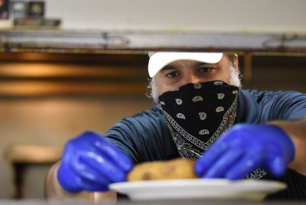Martin Rendon prepares a baked potato on Wednesday at The Veranda in Starkville. All staff members are required to wear face masks and gloves while they work. / Photo by: Claire Hassler/Dispatch Staff