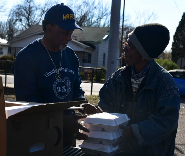 """Andy Stewart adds a meal to a stack Vallery Hampton planned to take to her family Nov. 28 in Columbus. Stewart helped deliver meals on the North side of town. Volunteers stopped the truck to pass out meals each time residents in the area waved it down. While on this particular delivery run, the volunteers had more people in need in meals than they had meals. """"We'll be back. We have to go grab more,"""" they assured the last few they passed. / Photo by: Jennifer Mosbrucker/Dispatch Staff"""