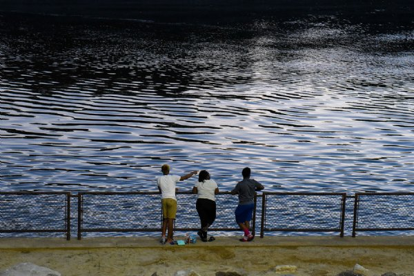 From left, Jewelee Hill, Sherrita Hill and Lazeric Phillips watch as a boat passes through the Tom Bevill Lock and Dam on June 18 in Pickensville. The trio grew up together in the Pickensville area. Jewelee and Sherrita are cousins, though Sherrita jokes that she doesn't know him. Lazeric and Jewelee have been best friends since middle school. / Photo by: Claire Hassler/Dispatch Staff