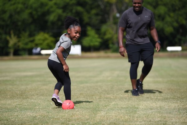 Samauria Martin, 6, passes a soccer ball to her dad, Justin Martin, on Saturday at the River Walk Soccer Complex in Columbus. Samauria also rode bikes with her twin brothers, Landon and Bryan, both 3. / Photo by: Claire Hassler/Dispatch Staff