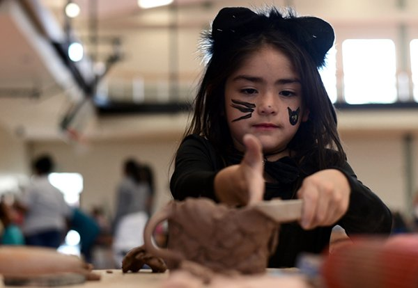 "Stella Bastow, 6, makes a mug with dog ears during Art in the Park Oct. 26 at the Starkville Sportsplex. ""I just came up with it in my head,"" Bastow said. She came to the event with her mom and brother. / Photo by: Jennifer Mosbrucker/Dispatch Staff"