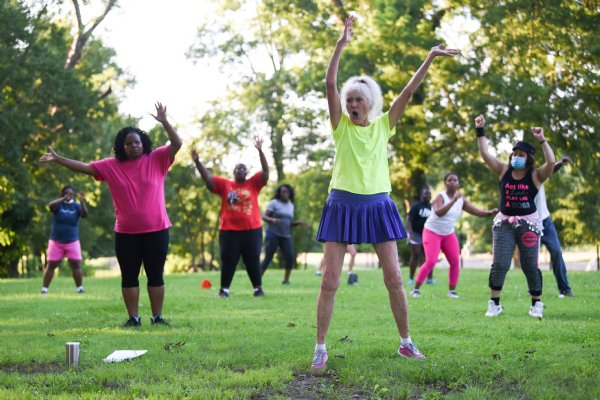 Bonnie Partridge leads a Zumba class on Tuesday evening at the River Walk Soccer Complex in Columbus. About 25 people came to follow along to upbeat music as the sun went down. / Photo by: Claire Hassler/Dispatch Staff