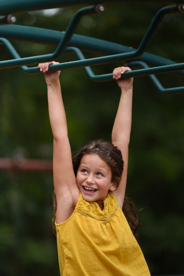 Reese Wooten, 7, swings on the monkey bars on July 29 at Oak Hill Academy in West Point. / Photo by: Claire Hassler/Dispatch Staff