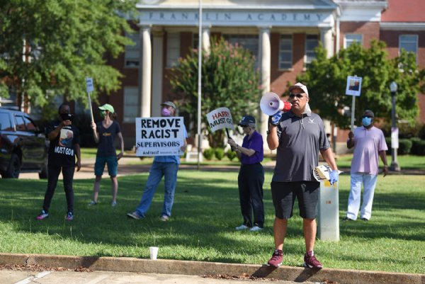 Jermaine Shanklin shouts into a megaphone on Monday during a county supervisors meeting outside the Lowndes County Courthouse in Columbus. About 11 protesters gathered during the meeting, though at its peak protests saw a crowd of 100 people. / Photo by: Claire Hassler/Dispatch Staff