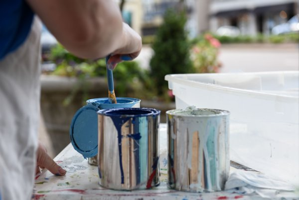 Amy Ballard dips her brush in a can of paint while painting the utility box at the intersection of Main Street and 6th Street on July 16 in Columbus. Painting the utility boxes downtown is part of a main street beautification project. / Photo by: Claire Hassler/Dispatch Staff