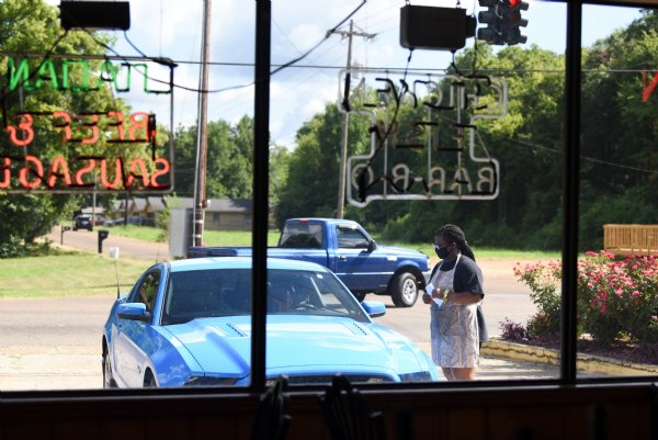 "Carolena Graham, 16, talks to a customer on Friday outside Skeet's Hotdogs in Columbus. Sylvia Graham, owner of Skeet's Hotdogs, said her staff is following all the CDC guidelines, but besides wearing masks and having their dining room closed, operations are fairly similar to what they were before COVID-19. ""I'm just doing what we're normally supposed to be doing anyway,"" Graham said. / Photo by: Claire Hassler/Dispatch Staff"