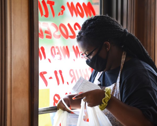 Carolena Graham, 16, takes a curbside pickup order outside on Friday at Skeet's Hotdogs in Columbus. Slyvia Graham, owner of Skeet's Hotdogs, said she had to cut staff hours for her four employees when the pandemic first hit, but now they are back to normal hours. / Photo by: Claire Hassler/Dispatch Staff