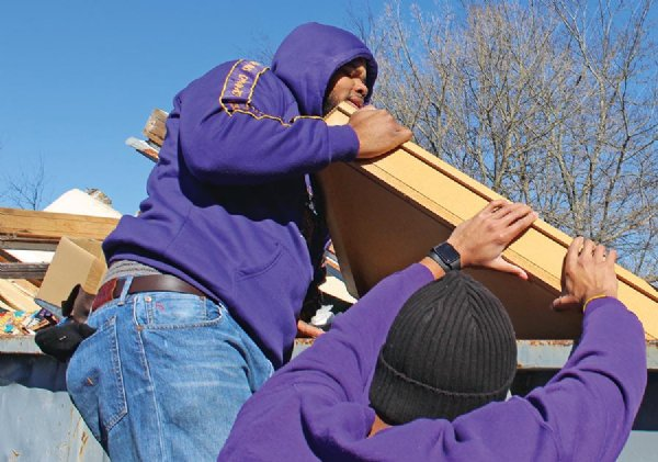 Shaun Kohlhein, left, and Reginald Williams III hoist a slab of wood into a dumpster at the Habitat for Humanity Warehouse on Rockhill Road. They were part of a group of 15 volunteers to clean up the warehouse as part of the Starkville MLK Day of Service on Monday. Both attend Mississippi State University and belong to the Omega Psi Phi service fraternity. / Photo by: Tess Vrbin/Dispatch Staff