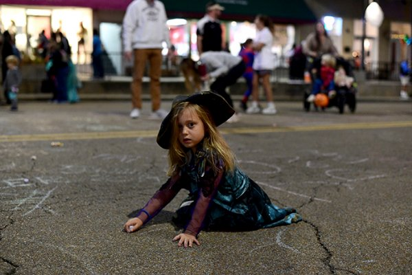 Sarah Shelton Little, 5, draws on Main Street during Pumpkinpalooza Thursday night in Starkville. She is dressed as pirate leader Uma from Disney's Descendants 3. / Photo by: Jennifer Mosbrucker/Dispatch Staff