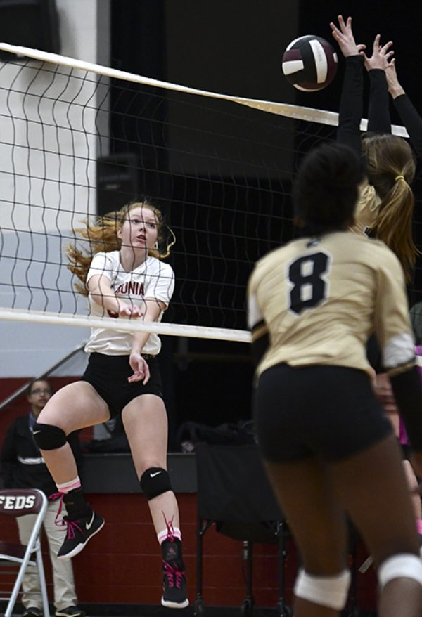 Caledonia's Zoe Hansen, left, spikes the ball over the net as defenders attempt to block the ball Oct. 10 at Caledonia High School. / Photo by: Jennifer Mosbrucker/Dispatch Staff