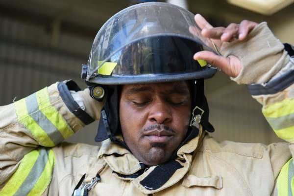 Justin Martin puts on his helmet on Friday during training outside Fire Station 3 in Columbus. Martin has been a firefighter for three years. / Photo by: Claire Hassler/Dispatch Staff