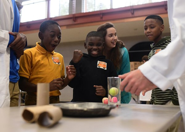 From left to right, Kameron Kidd, 9, KeJuan Jackson, 9, Danza Thomason and Jacoby Edwards, 9, react to an inertia activity taught by Mississippi School for Mathematics and Science students Tejus Kotikalapudi, 16, and Chandler Bryant, 16, during the MSMS Science Carnival Oct. 30 at Pohl Gymnasium. The activity demonstrated inertia as the metal pan was moved from underneath plastic eggs. Although the pan moved in one direction, the eggs fell straight down. / Photo by: Jennifer Mosbrucker/Dispatch Staff