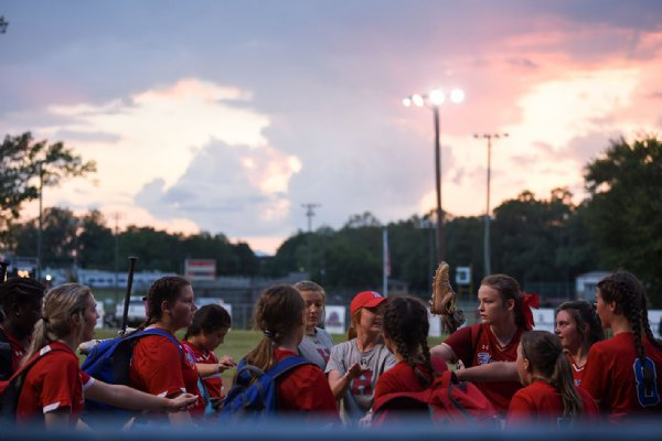 The Lady Patriots huddle for a cheer after winning their softball game against Oak Hill Academy on Monday at Oak Hill Academy in West Point. / Photo by: Claire Hassler/Dispatch Staff