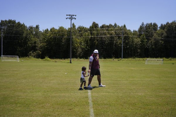Jeffery Simmons hands his son, Jeffery Ajary Simmons, 2, a Gatorade while taking a break during the Jeffery Simmons Football camp on Saturday at the Starkville Sportsplex in Starkville. / Photo by: Anto Tavitian/Dispatch Staff