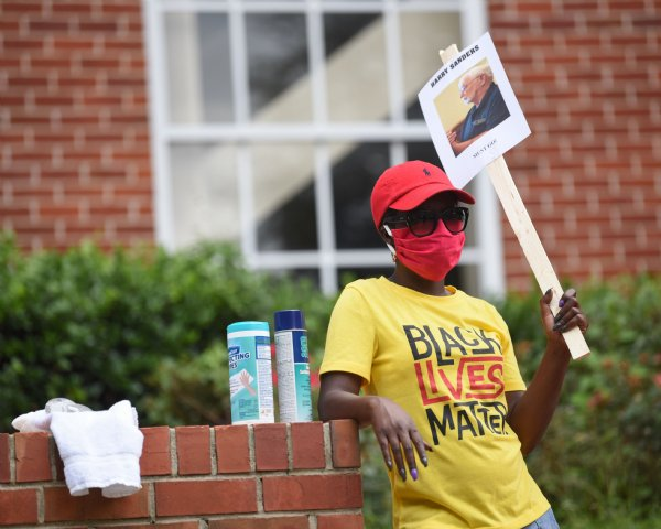 Tamika Jones stands next to disinfecting wipes and sanitizing spray during the Equality and Justice March on Saturday in Columbus. All of the protesters wore masks during the march and rally as a precaution due to COVID-19. / Photo by: Claire Hassler/Dispatch Staff