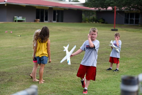 From left, Madison Coggins, 6, and Reese Wooten, 7, talk while Colton Blissard, 7, and Cameron Blissard, 5, prepare to throw their toy airplanes on July 29 outside Oak Hill Academy in West Point. / Photo by: Claire Hassler/Dispatch Staff