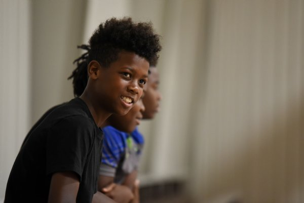 Antonious Hollaway, 12, smiles while watching his friends play basketball on Thursday at the Crawford Community Center. At 4 p.m. the gym is disinfected for an hour as a COVID-19 precaution. / Photo by: Claire Hassler/Dispatch Staff