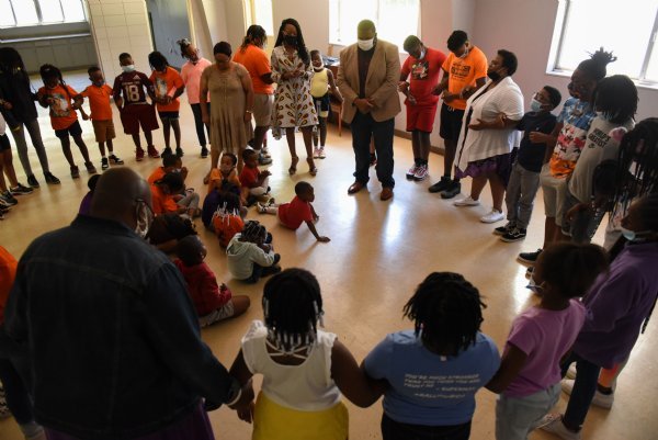 Community leaders, from left, Jackie Rogers, Tammie Tubbs and Jarvis Boyd stand in the middle of a prayer circle during Ms. Smith's Academic Summer Camp on July 23 at the Needmore Center in Starkville. Before praying, the three led a panel discussion about how to be your best self and have confidence. / Photo by: Claire Hassler/Dispatch Staff