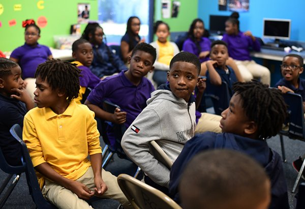 In focus from left to right, Michael Brewer, Gemí Moody, Aquavious Sherrod and Tyson Sims turn around to look at mentors who came to the event from Columbus Air Force Base as they are introduced Nov. 1 at the Boys & Girls Club of Columbus. / Photo by: Jennifer Mosbrucker/Dispatch Staff