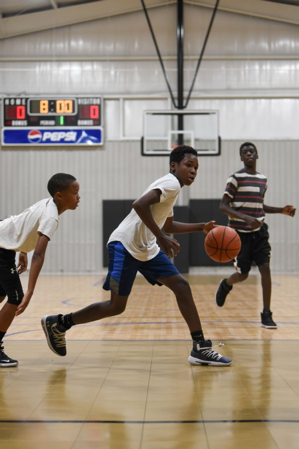Tyler Smith, 13, dribbles while Anquarius Outlaw, 11, tails after him on Thursday at the Crawford Community Center. Over two dozen boys from Crawford and surrounding towns took to the court to play. / Photo by: Claire Hassler/Dispatch Staff