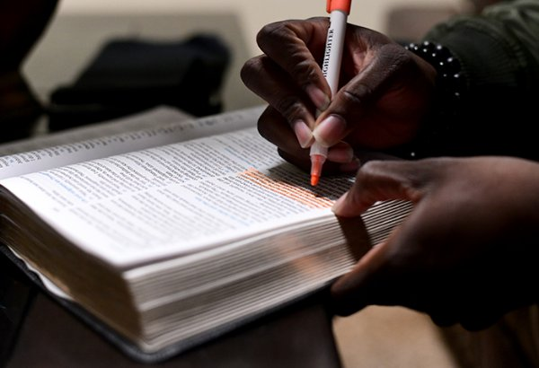 Bishop R.J. Matthews highlights a verse in his bible prior to preaching on the second night of Glory on the Grounds. Before preaching, Matthews takes a few minutes to pray and prepare himself. / Photo by: Jennifer Mosbrucker/Dispatch Staff