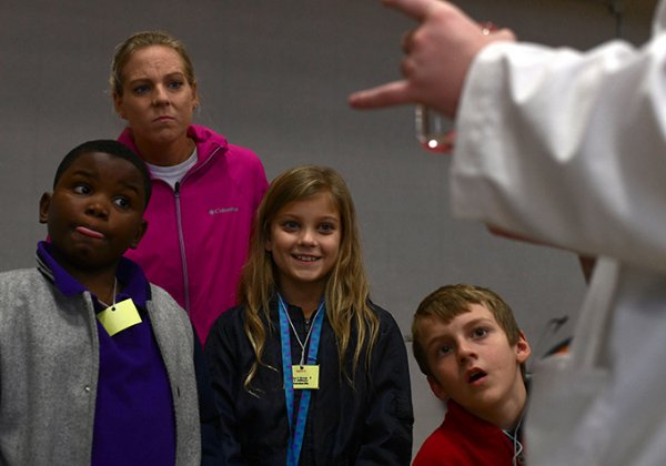 From left to right, Kyren Walters, 9, Becky Cox, Rylee Cox, 9, and Bentlee Baucom, 8, watch as Mississippi School for Mathematics and Science student Garrett Wells, 18, scoops hydrophobic sand from a beaker during the MSMS Science Fair Oct. 30 at Mississippi University for Women's Pohl Gymnasium. / Photo by: Jennifer Mosbrucker/Dispatch Staff