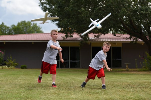 Colton, 7, and Cameron Blissard, 5, throw airplanes on July 29 outside Oak Hill Academy in West Point. / Photo by: Claire Hassler/Dispatch Staff