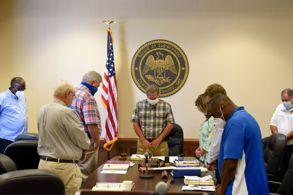 Lowndes County Supervisors pray before starting their meeting on Monday at the Lowndes County Courthouse in Columbus. District 5 County Supervisor Leroy Brooks stands in the corner of the room instead of at the table as an act of protest against District 1 County Supervisor Harry Sanders and the racist remarks he made about African Americans on June 15. / Photo by: Claire Hassler/Dispatch Staff