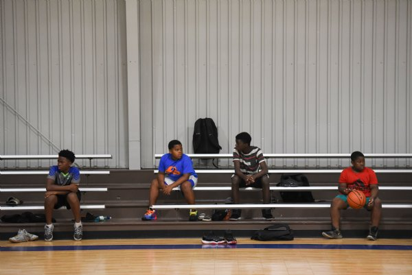From left, Taylan Brown, 14, Kylan Ellis, 12, Tyrome Scales, 13, and Bryson Sharp, 8, sit on the bleachers and watch basketball on Thursday at the Crawford Community Center. The February 2019 tornado destroyed Crawford's community center, leaving the town without an indoor basketball facility. / Photo by: Claire Hassler/Dispatch Staff