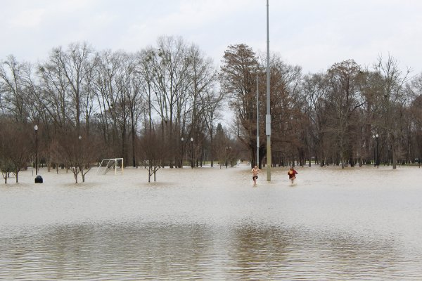 Will Waggoner and Franki Hill run through the water covering the Columbus Soccer Complex on Wednesday afternoon. They each wanted to see how far out into the water the other would go. / Photo by: Isabelle Altman/Dispatch Staff