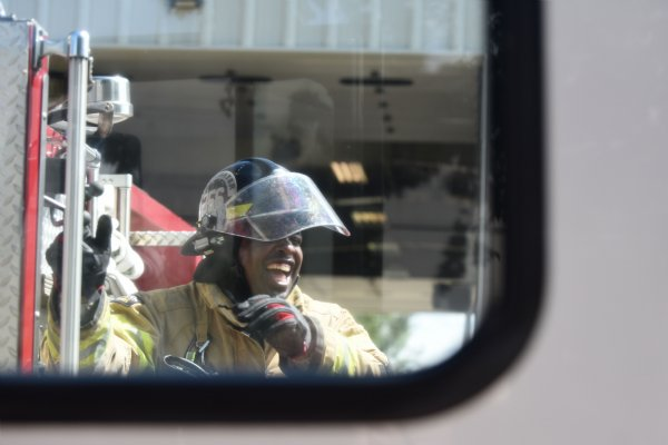 Justin Martin laughs while wrapping up his training for the day on Friday outside Fire Station 3 in Columbus.  Martin's mother used to be a dispatcher for the Columbus Fire Department, and Martin fondly remembers spending time at the station as a kid. / Photo by: Claire Hassler/Dispatch Staff