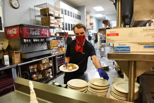 Luke Cosby picks up plates to take out to the dining room on Wednesday at The Veranda in Starkville. Martin Rendon, The Veranda's manager, said they are currently operating with one third of their usual staff, and that they had as few as six staff total in April. / Photo by: Claire Hassler/Dispatch Staff