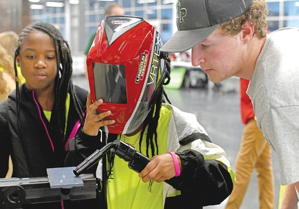 New Hope Middle School students Skyler Bell, 13, left, and Jazmin Ross, 13, learn about welding from West Point Career Technical Center student Wesley Gaskin, 17, during the FORGE Foundation's career expo Wednesday at East Mississippi Community College's Communiversity. Gaskin is in his third year of welding classes.