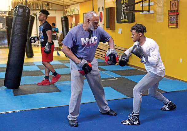 Oliver Miller puts on punching mitts to work with his grandson Zion Reed, 16, during practice on Thursday at Miller's Boxing and Taekwondo Gym in Columbus. Reed has been training at his grandfather's gym for much of his life.
