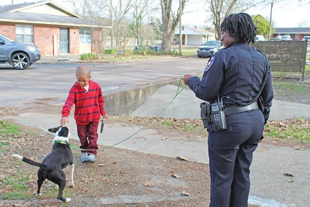 Denzel Riley, 4, son of Bricy Green, pets Star Gazer, a pit bull mix from the Oktibbeha County Humane Society, at Brookville Garden Apartments on Thursday. Starkville Police Officer Angelica Colbert, right, took Star Gazer around town as part of the Dog's Day Out program to facilitate community engagement.