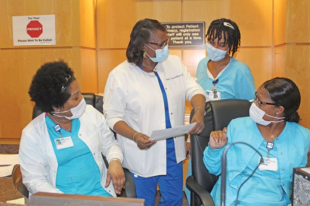 Registered nurse Betty Cunningham, second from left, chats with associate nurses Audrey Moore, Shan Williams and Amberial Covington at the help desk in Outpatient Pavilion at Baptist Memorial Hospital-Golden Triangle Friday afternoon. Cunningham has worked at Baptist for 40 years, and says the people she works with have always been like one big family to her.