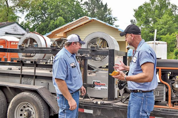 Jerry Wall, left, and Mel DuBois of Magnum Metals of Nettleton, prepare their fabricating machine to begin installation of a new steel roof at a house on 12th Avenue North in Columbus Tuesday. The machine shapes and cuts the rolled steel to exact specifications. The steel was donated by Steel Dynamics with Mississippi Steel Processing also prepping the steel. Magnum Metals and Ervin Brothers roofing are providing their services free of charge for the work, which is a Columbus Lowndes Habitat for Humanity Project. The house is the first Habitat building to feature a steel roof.