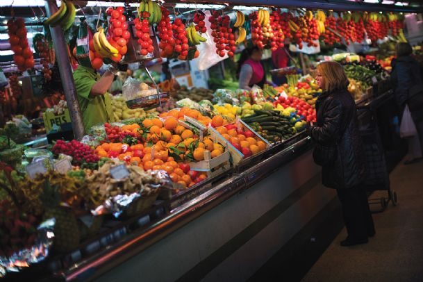 In this Thursday Jan. 17 file photo, a woman buys fruit at a market in Barcelona, Spain.