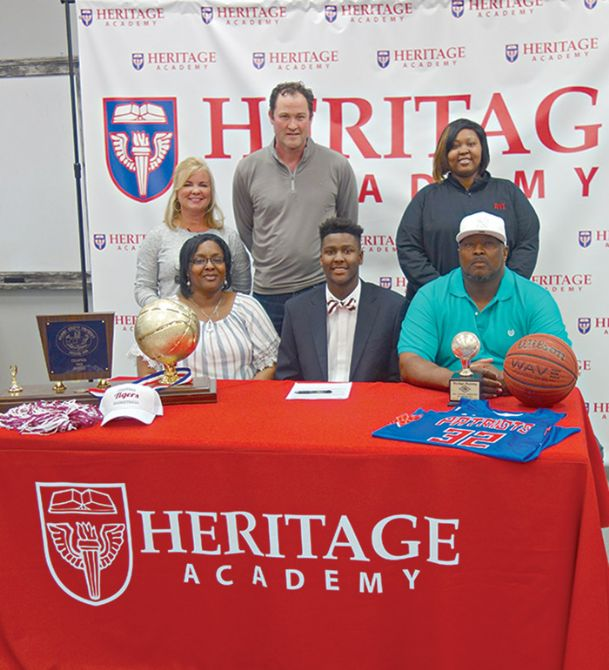 Heritage Academy Heritage Academy senior Cameron Bell signed a letter-of-intent Tuesday to attend school and play basketball at Coahoma Community College. Joining him on signing day were Chekila Young, left, his mother, and Steven Bell, his dad. Back row: Betsy and Chad Altmyer, and Cameron's sister, Alexus Bell.