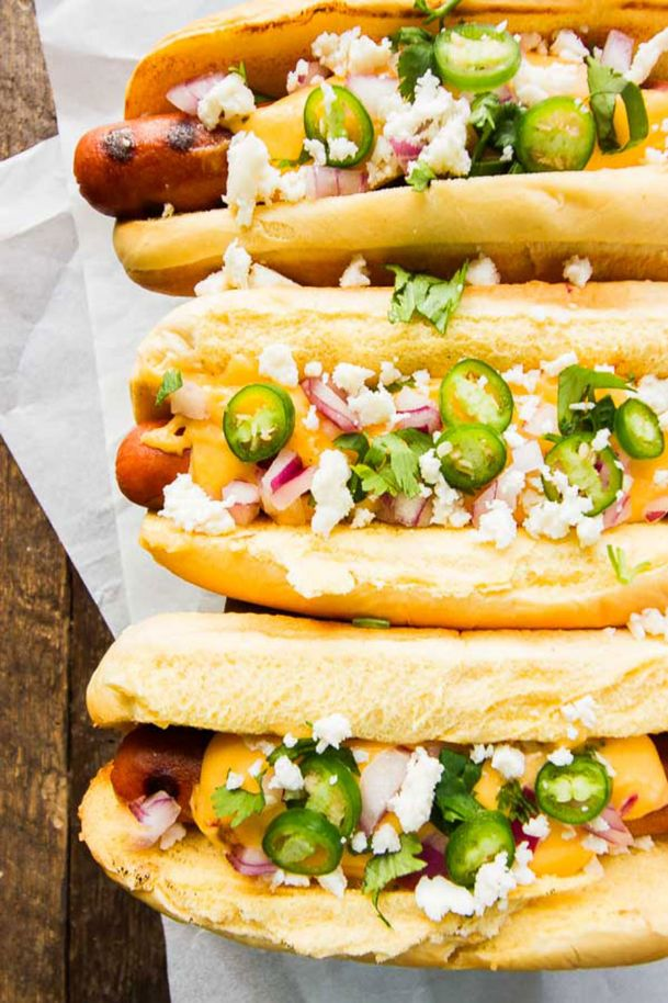 Summer is the perfect time to serve up specialty hot dogs like these Mexican gourmet cheese dogs with cheddar and queso fresco cheeses, red onions, serrano peppers, crumbled bacon and more.