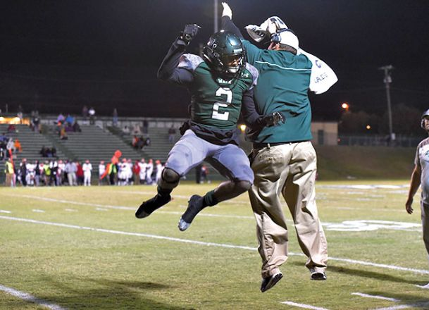 West Point High School's Marcus Murphy (2)  celebrates with a coach Friday during a victory against Callaway.
