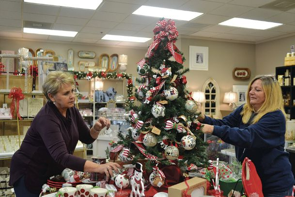 The Purple Elephant employees Dixie Belue and Sherri Dyer decorate a Christmas tree with handmade ornaments Monday afternoon. The Purple Elephant and other local businesses brought in the holiday season with Black Friday and Shop Small Saturday.