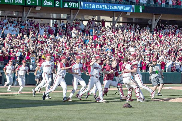 Arkansas Razorbacks players rush onto the field after defeating the Mississippi Rebels at Baum-Walker Stadium on Monday.