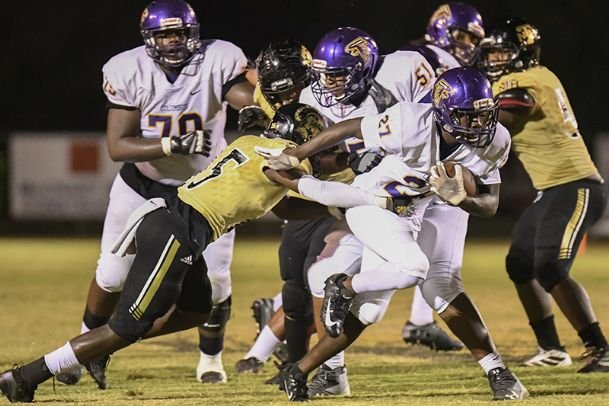 Columbus running back Karon Hawk (27) gets past New Hope defensive back Hayden Harris (25) during last year's game between the two schools on Sept. 27, 2019, in New Hope. The Falcons and Trojans will resume the rivalry Friday in Columbus.
