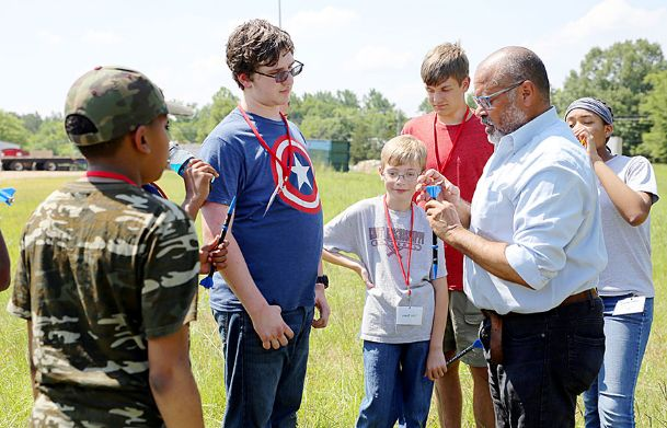 East Mississippi Community College Board of Trustees member Greg Stewart, at right, who also works for Aurora Flight Sciences, demonstrates how to prepare a model rocket for launch to students enrolled in EMCC's Camp AMP. The students are, from left: Caledonia Middle School student Ethan Jamison, 11; Armstrong Middle School student Chase Dodd, 13; Oak Hill Academy student Tyler Bauer, 11; Eupora High School student Brady Tabb, 14; and Columbus Christian Academy student Eboni Sherrod, 11.