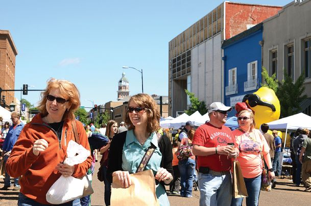 Day Smith, of Starkville, left, and her daughter, Emily Wolff, of Minnesota, walk down Main Street with the crowd during the Market Street Festival Saturday looking at craft vendors. They were on the hunt for something different and fresh to buy.