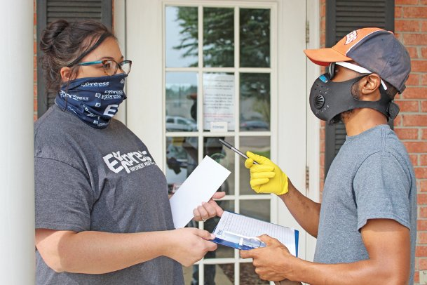 Tabatha Estes, left, an employment specialist at Express Employment Professionals, helps Starkville resident Kwame Bardwell fill out an application form Friday. The agency matches people with potential employers based on skill sets, background checks and references. All industries' hiring practices have adapted to the COVID-19 pandemic, and Express Employment Professionals started holding drive-through job fairs in August to help people make connections with limited interpersonal contact.