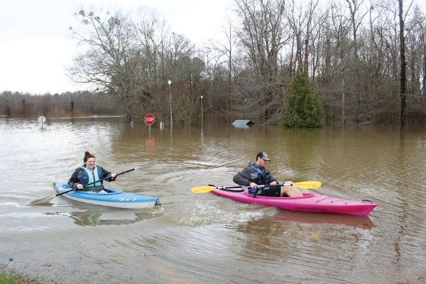 Ann Marie and Carson Miller kayak from their home on Bigbee Loop to the west end of Main Street on Thursday afternoon. They evacuated Tuesday, due to rising flood waters, and said the water was about two feet away from their home, which is built on stilts.